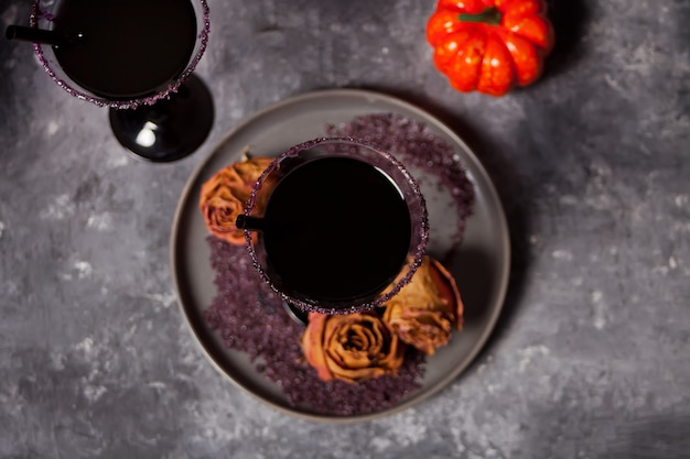 Two glasses with black cocktail, dried roses, pumpkin for halloween party on dark