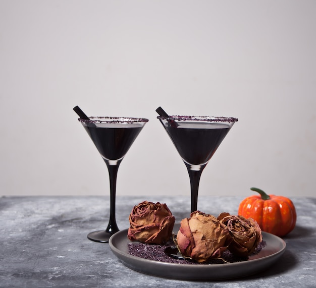 Two glasses with black cocktail, dried roses, pumpkin for halloween party