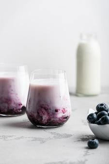 明るい壁にブルーベリーミルクセーキと新鮮なブルーベリーのグラス2杯
