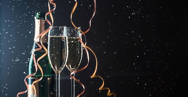 Два бокала с шампанским и бутылка на темном фоне со снегопадом. изображение с копией пространства
