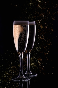Two glasses with champagne on bokeh background