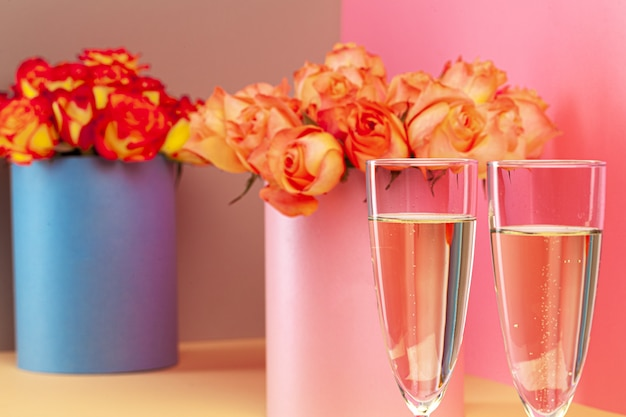 Two glasses with champagne and and bouquet of roses