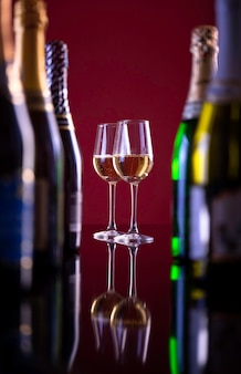 Two glasses with champagne on a burgundy background. a glass next to bottles of alcohol