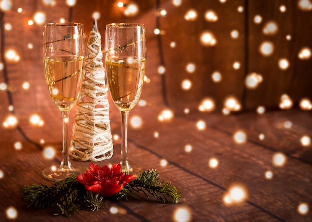 Two glasses with champagne and christmas decoration and lights