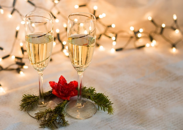 Two glasses with champagne and christmas lights card with space to write