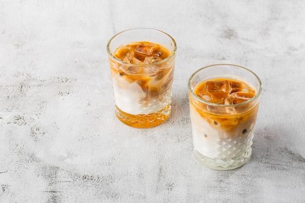차가운 양조 커피와 우유 밝은 대리석 백그라운드에 고립 된 두 잔. 오버 헤드보기, 복사 공간. 카페 메뉴 광고. 커피 숍 메뉴. 가로 사진.