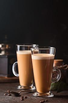 Два стакана с холодным кофе латте макиато на столе против черного