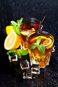 Two glasses with cold traditional iced tea with lemon, mint leaves and ice cubes