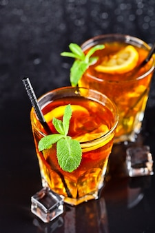 Two glasses with cold traditional iced tea with lemon, mint leaves and ice cubes.