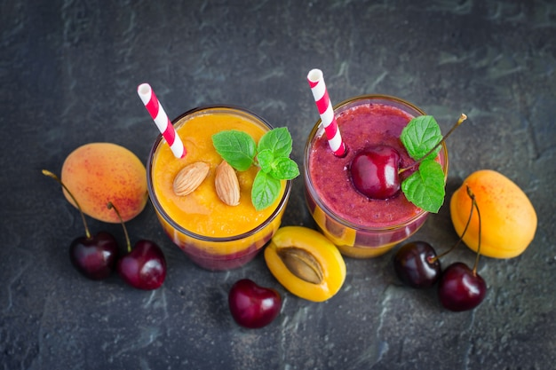 Two glasses with colored cherry apricot smoothies
