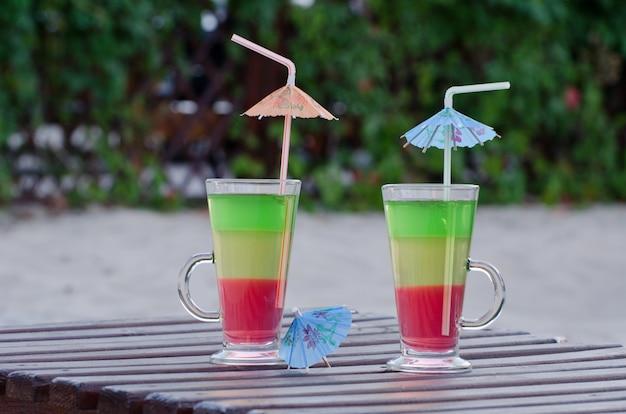 色付きのカクテルと裏庭の木製デッキチェアにストローで2杯