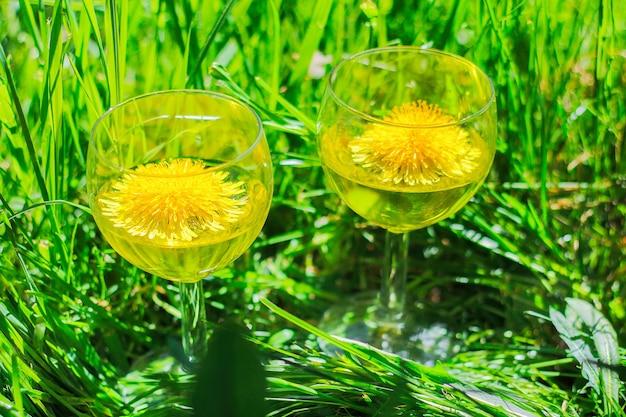 草の上にタンポポのワインとグラス2杯