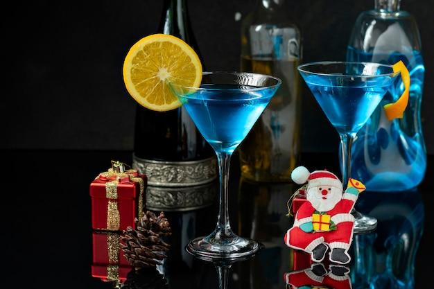 オレンジで装飾されたディンクブルーの2つのガラス、テーブルの上のクリスマスの装飾