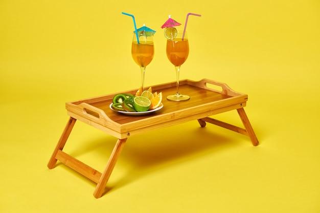Два бокала с экзотическими летними коктейлями, украшенные коктейльным зонтиком и тарелкой