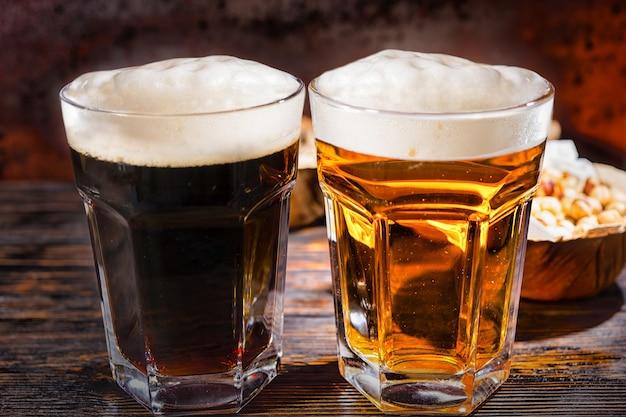 暗い木製の机の上にピスタチオとプレートの近くに新たに注がれたダークビールとライトビールのグラス2杯。食品および飲料の概念
