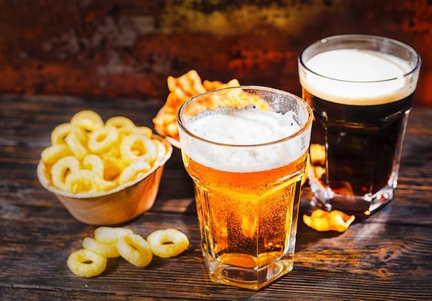 暗い木製の机の上にスナックとチップスが入ったプレートの近くに、新しく注がれた明るいビールと暗いビールが入ったグラス2杯。食品および飲料の概念