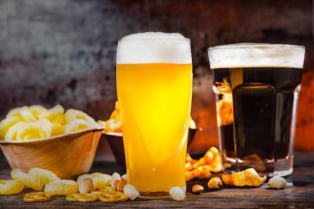 暗い木製の机の上にチップスと散らばったスナックが入ったプレートの近くに、ろ過されていない明るいビールと暗いビールを注ぎたてのグラス2杯。食品および飲料の概念