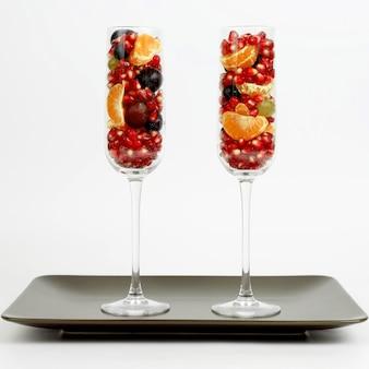 白い背景の上の茶色のプレートに果物と2つのグラス。健康的な新鮮な野菜と食品