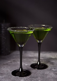 Two glasses with green zombie cocktail for halloween party on the gray background
