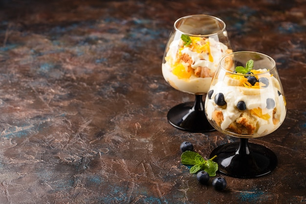 Two glasses with healthy homemade layered dessert trifle with orange, blueberry, biscuit, yogurt and granola. place for text