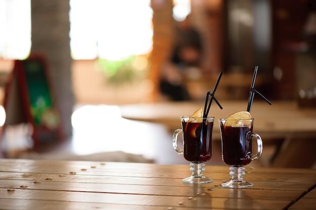 カフェの木製テーブルにホットホットホットワインとグラス2杯