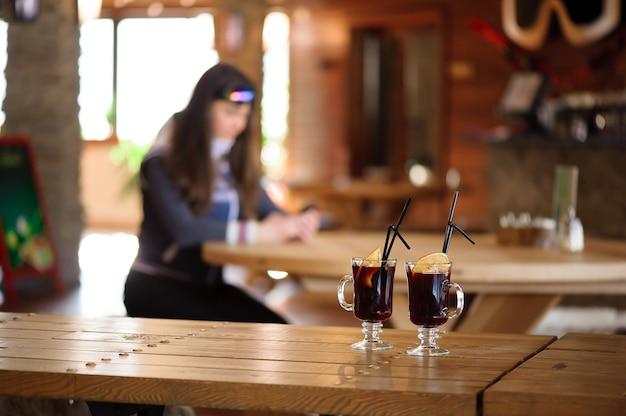 Два бокала с горячим вкусным глинтвейном на деревянном столе в кафе