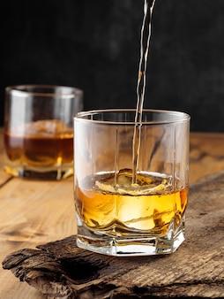 古い木製のテーブルにアイスキューブとウイスキーのグラス2杯。スペースをコピーします。