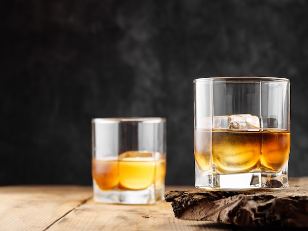 Two glasses with ice cube and whiskey on an old wooden table. copy space.