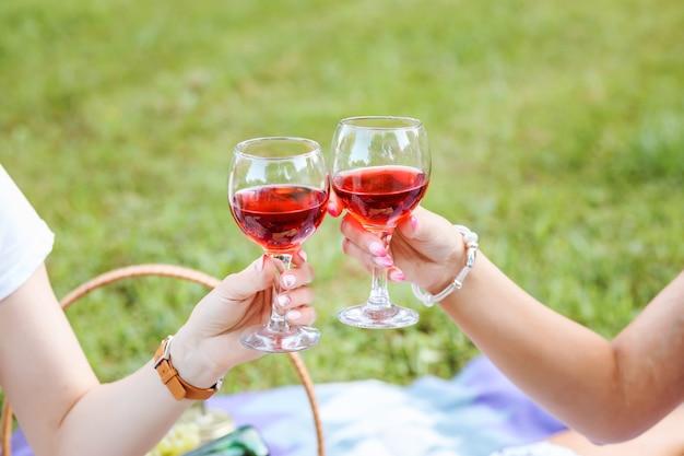 녹색 잔디에 여자 손에 주스 또는 와인 두 잔