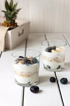 Два стакана с слоистыми овсяными хлопьями и фруктами на белом деревянном столе. концепция здорового завтрака и здорового образа жизни.