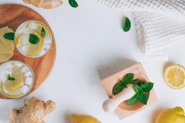 レモネードと料理の材料が入ったグラス2杯。生姜、レモン、ミント、白い表面の氷。木製トレイ、乳鉢と乳棒。フラットレイ。コピースペース