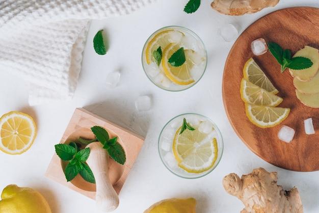 Два стакана с лимонадом и ингредиентами. имбирь, лимон, мята, лед. деревянный поднос, ступка и пестик. плоская планировка