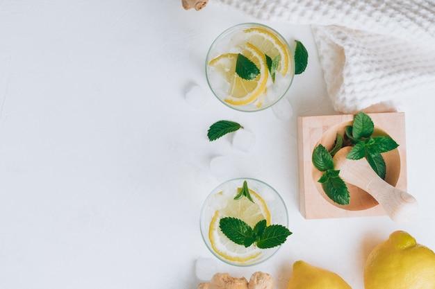 Два стакана с лимонадом. ингредиенты имбирь, лимон, мята, лед на белой поверхности. ступка, пестик. плоская планировка. копировать пространство