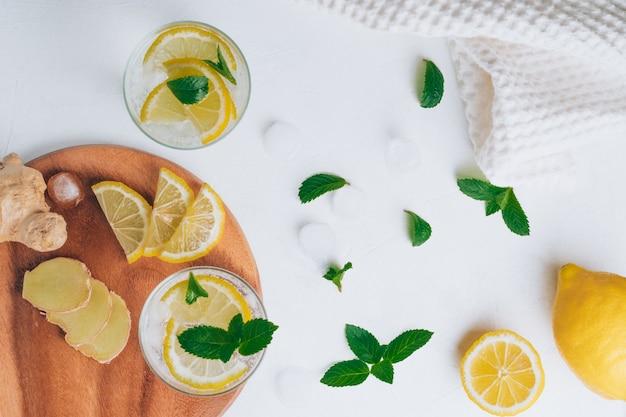 レモネードとグラス2杯。材料生姜、レモン、ミント、白い表面の氷。木製トレイ。フラットレイ