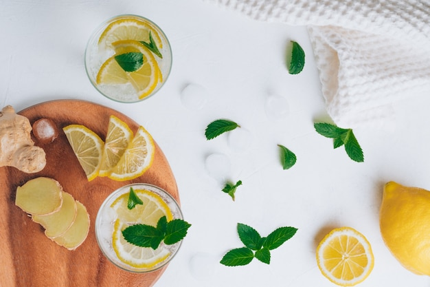 Two glasses with lemonade. ingredients ginger, lemon, mint, ice on white surface. wooden tray. flat lay