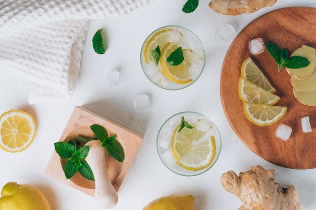 Two glasses with lemonade and ingredients. ginger, lemon, mint, ice. wooden tray, mortar and pestle. flat lay