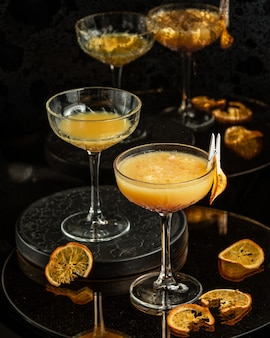 Two glasses with long stem of orange cocktail with pulp