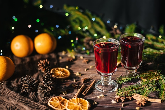 Two glasses with mulled wine on the table with orange slices and spices