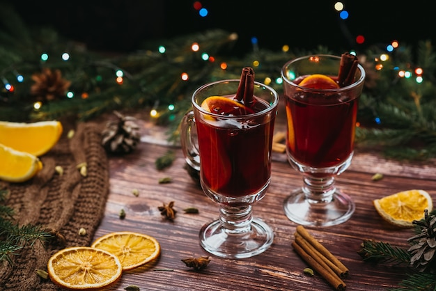Two glasses with mulled wine on a wooden table with fir branches new year