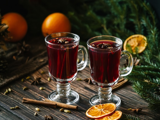 Two glasses with mulled wine on a wooden table with orange, cinnamon, cardamom, anise stars. traditional winter hot alcoholic drink