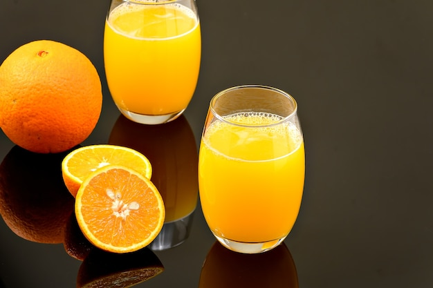 Two glasses with orange juice on a reflective dark surface