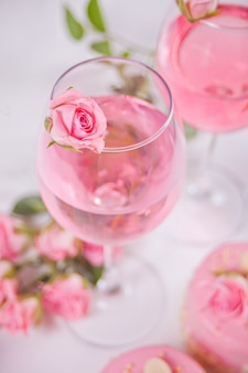 Two glasses with pink grape wine with rose flowers. romantic dinner concept.