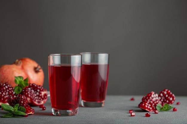 灰色のコンクリートのテーブルの上にザクロジュースを入れたグラス2杯が立っています。近くにはザクロのスライスがいくつかあります。