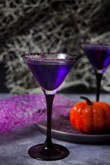 Two glasses with purple cocktail for halloween party on dark