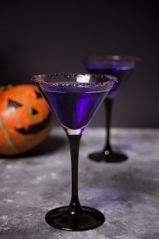 Two glasses with purple cocktail, pumpkin for halloween party  dark