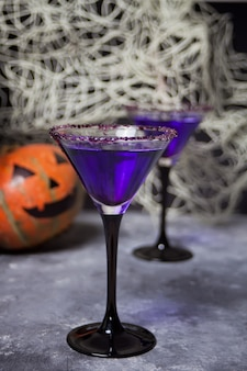 Two glasses with purple cocktail, pumpkin for halloween party