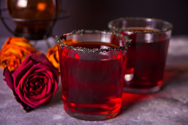 Two glasses with red cocktail, dried roses for halloween party on the dark