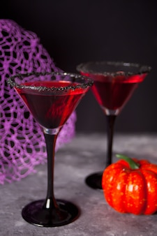 Two glasses with red cocktail for halloween party on dark