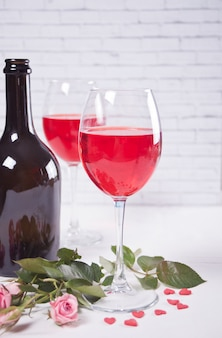 Two glasses with red grape wine with bottle and roses on the background. romantic dinner concept.