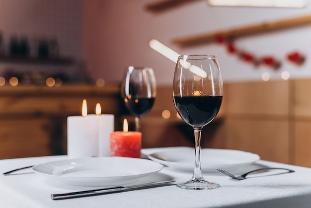 Two glasses with red wine and burning candles on a served table close-up